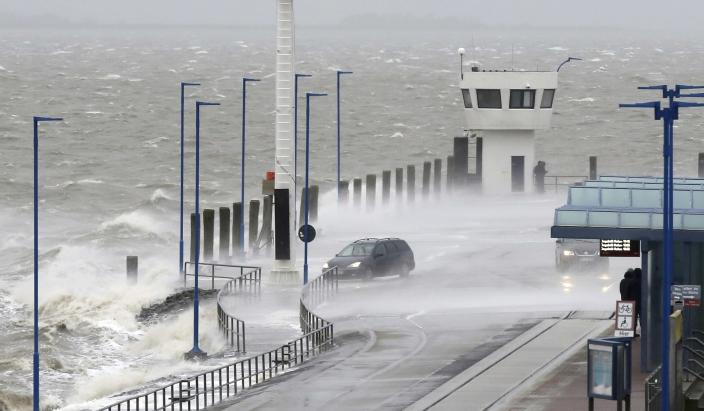 Water splashes on the pier of the ferry pier in Dagebuell, northern Germany, Sunday, Feb. 9, 2020. Weather warnings issued across northern Europe as the storm with winds expected to reach hurricane levels batters the region. (Bodo Marks/dpa via AP)