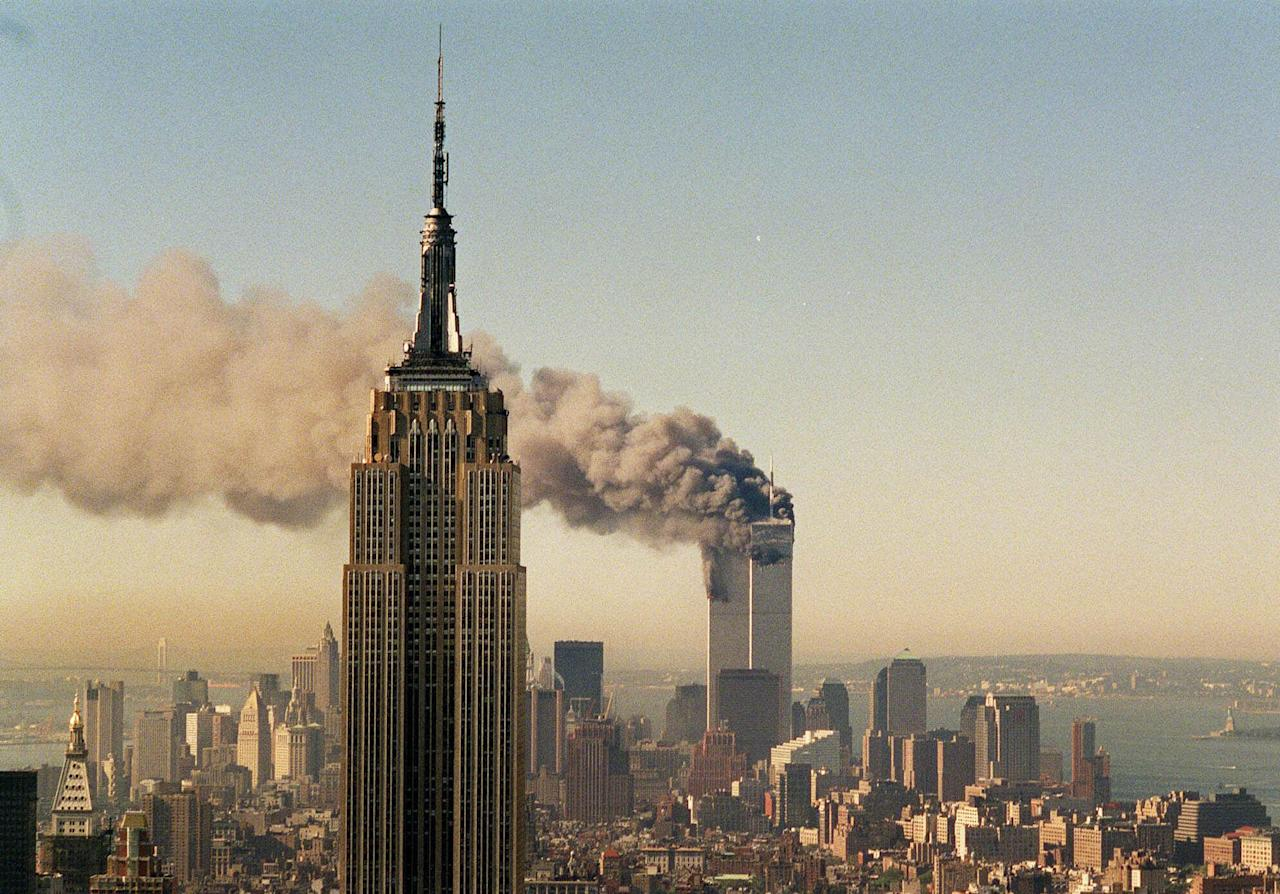 FILE- This Sept. 11, 2001 file photo shows the twin towers of the World Trade Center burning behind the Empire State Building in New York. The book world plans a low-key remembrance of the upcoming 10th anniversary of the Sept. 11 terrorist attacks. (AP Photo/Marty Lederhandler, FILE)