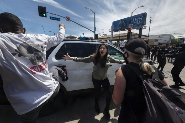 A protester, center, tries to stop others from attacking a police vehicle during a protest over the death of George Floyd in Los Angeles, May 30, 2020. The image was part of a series of photographs by The Associated Press that won the 2021 Pulitzer Prize for breaking news photography. (AP Photo/Ringo H.W. Chiu)