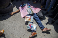 FILE - In this Sept. 1, 2020 file photo, a demonstrator lies on the pavement imitating the lifeless body of Bar Association President Monferrier Dorval, covered with photos of the murder scene, during a protest to demand justice for Dorval, who was fatally shot in Port-au-Prince, Haiti. On Friday, July 9, 2021, The Associated Press reported on claims circulating online wrongly asserting that a photo of a man lying on the pavement in blue pants covered in blood shows Haitian president Jovenel Moïse after his assassination early Wednesday. The photo is really from the Aug. 29, 2020, killing of Dorval, a prominent lawyer who was shot outside his home. (AP Photo/Dieu Nalio Chery, File)