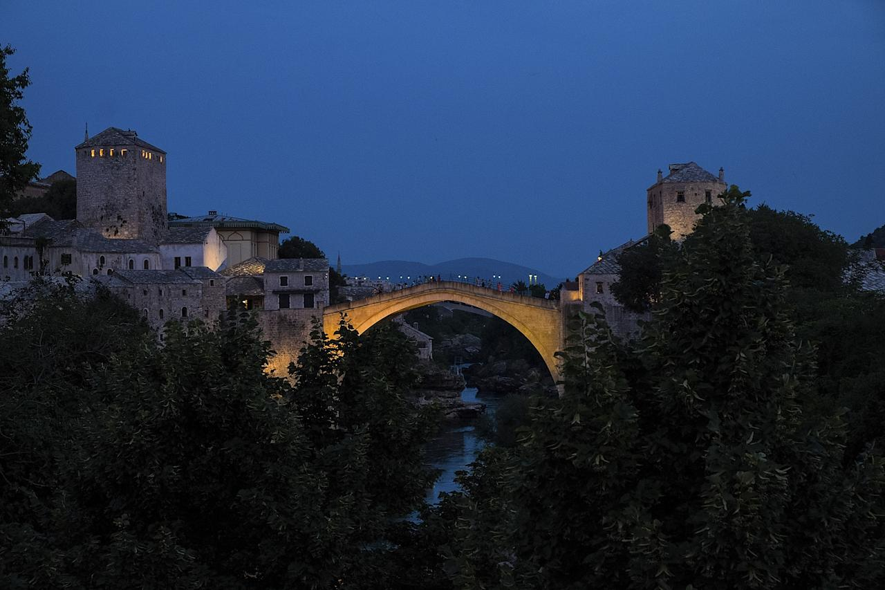 MOSTAR, BOSNIA AND HERZEGOVINA - JUNE 28: Light illuminates the Old Bridge standing as the city of Mostar remembers the 1993 conflict on June 28, 2013 in Mostar, Bosnia and Herzegovina. The Siege of Mostar peaked in 1993 during the Croat-Bosniak conflict lasting eighteen months as fighting took place as Bosnia and Herzegovina declared independence from Yugoslavia. The city was divided in half between the two battling armies. Mostar, dating back over four hundred years, was mostly destroyed through the fighting. Although reconstruction has slowly commenced in the last decades, evidence of the war remains in bullet ravaged buildings still standing throughout the city. (Photo by Marco Secchi/Getty Images)