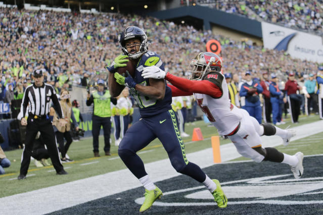 Seattle Seahawks wide receiver Tyler Lockett, left, catches a pass for a touchdown as Tampa Bay Buccaneers defensive back Jamel Dean, right, attempts the tackle during the first half of an NFL football game, Sunday, Nov. 3, 2019, in Seattle. (AP Photo/John Froschauer)