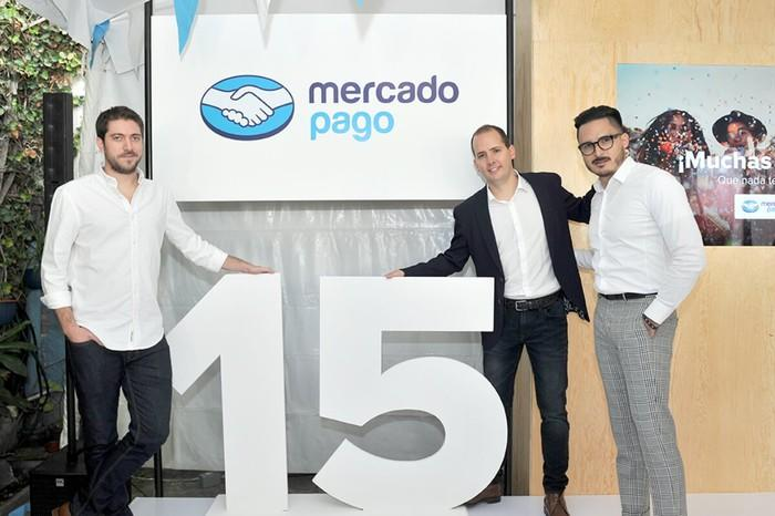 Three people in front of a MercadoPago sign and the number 15.