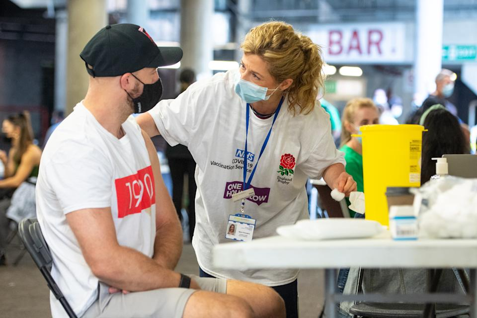 A man receives a coronavirus vaccination at Twickenham rugby stadium amid doubts over the 21 June unlocking date. (PA)