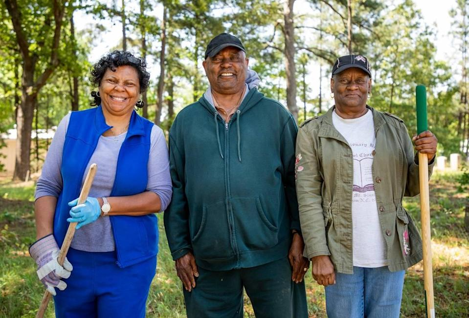 From left, Deborah Lofton, Clement Harris, and Ethel LaVerne Patterson stand for a portrait after cleaning the graves of their family members in the Oak Grove Cemetery, which was founded by freed African-Americans after the Civil War and now has lost more of its tree buffer to widening of the I-440 Beltline, that separated it from the rest of the Method community in the 1960s, on Saturday, May 8, 2021, in Raleigh, N.C.