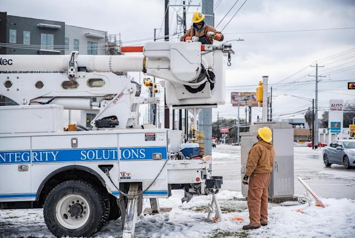 Electrical workers repair a power line in Austin in February. Cold weather took down the electricity grid in Texas this winter, but it showed how deadly a cyberattack that did the same thing could be. More than a hundred people died during the Texas outages.
