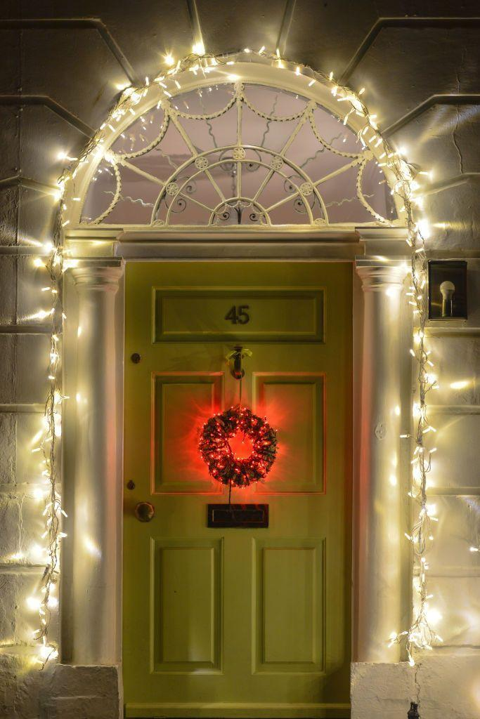 <p>From the string-lit archway to the glowy red wreath, this outdoor setup shines for the holidays. </p>