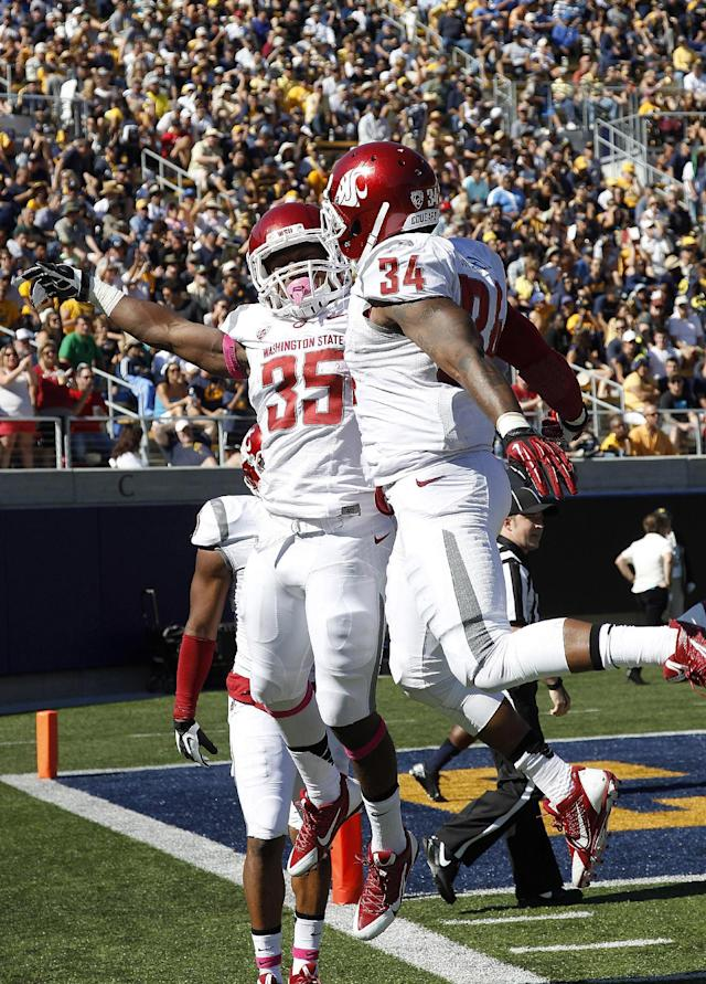 Washington State running back Marcus Mason (35) celebrates with teammate Teondray Caldwell (34) after Mason scored a touchdown against California during the first half of an NCAA college football game in Berkeley, Calif., Saturday, Oct. 5, 2013. (AP Photo/Tony Avelar)