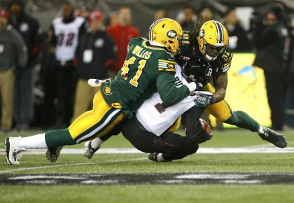 Ottawa Redblacks quarterback Henry Burris (1) is sacked by Edmonton Eskimos' Odell Willis (41) and Marcus Howard (91) during the CFL's 103rd Grey Cup championship football game in Winnipeg, Manitoba, November 29, 2015. REUTERS/Mark Blinch