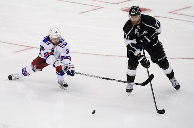 New York Rangers right wing Mats Zuccarello, left, of Norway, knocks the puck away from Los Angeles Kings center Jeff Carter during the third period in Game 1 of the NHL hockey Stanley Cup Finals, Wednesday, June 4, 2014, in Los Angeles. (AP Photo/Mark J. Terrill)