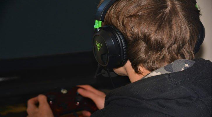 Image of a gamer with a headset facing a screen