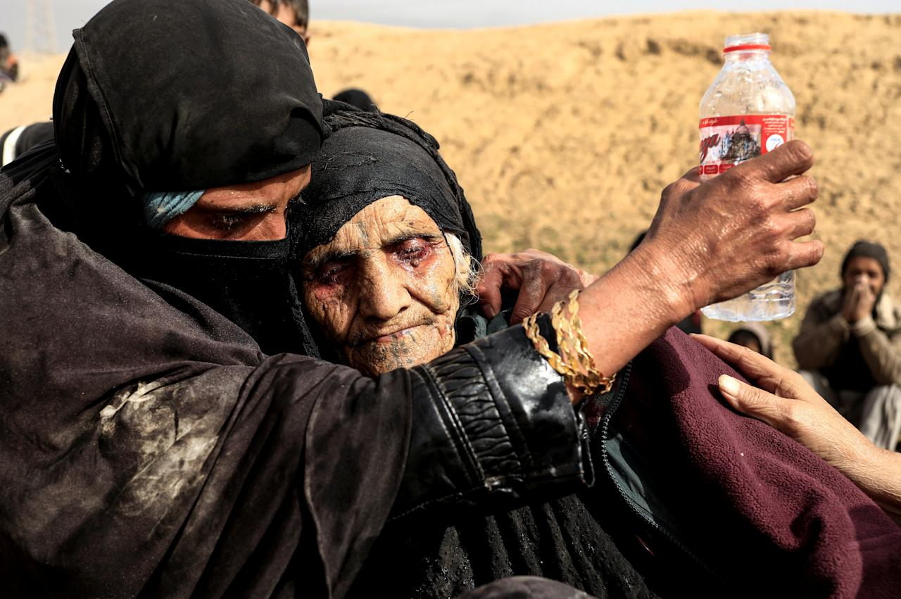 """Displaced Iraqi women who just fled their home, rest in the desert as they wait to be transported while Iraqi forces battle with Islamic State militants in western Mosul, Iraq, February 27, 2017. Zohra Bensemra: """"I took this picture in a desert on the outskirts of Western Mosul of 90-year-old Khatla Ali Abdallah after she fled the battle for Mosul. Her fearful eyes red with fatigue, Khatla was so exhausted she could not stand or even sit properly. She looked to me like she had not eaten or drank water for a long time. The moment was so emotional that I had tears in my eyes when I photographed Khatla. I felt bad because I could not do anything for her apart from taking pictures to show the world the agony and torment of people trying to flee Mosul to safety. I was sad too, imagining this woman as my own grandmother and feeling helpless to make her comfortable. When you face such a moment, you always think that it could happen to anyone of us. But despite all, Khatla looked beautiful to me, almost as if every wrinkle on her face told a story. I was fortunate to find her a few days later in a refugee camp after showing people my photograph of her. She has survived decades of turbulence in northern Iraq. She told me """"the fighting there is the worst I have ever seen"""". She had been carried across the desert by her grandsons, under sniper and mortar fire, one of thousands who braved the difficult and dangerous journey out of Islamic State's shrinking stronghold in western Mosul. Khatla made me smile when she expressed her remorse about her 20 chickens she had to leave behind. She had looked after them even while hiding from crossfire in her house's basement. Despite all the terror she experienced under IS rule, it had not destroyed her humanity - she said, 'Even animals deserve life.'"""" REUTERS/Zohra Bensemra/File Photo SEARCH """"POY STORY"""" FOR THIS STORY. SEARCH """"REUTERS POY"""" FOR ALL BEST OF 2017 PACKAGES. TPX IMAGES OF THE DAY."""