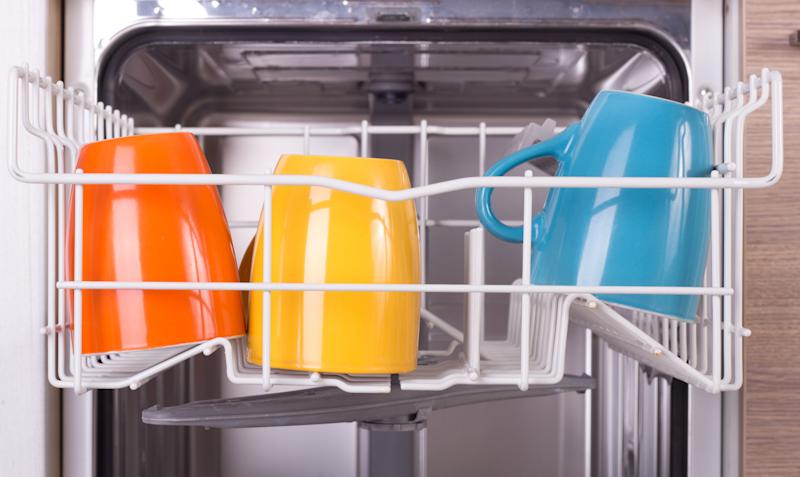 Close up of colorful cups in open dishwasher in kitchen