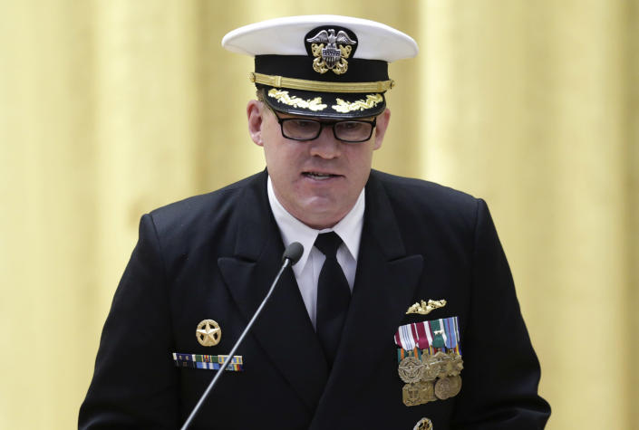 """Commander Rolf Spelker speaks at the decommissioning ceremony for the fire-damaged USS Miami nuclear submarine at the Portsmouth Naval Shipyard, Friday, March 28, 2014, in Kittery, Maine. Rear Adm. Ken Perry, commander of the submarine Group Two in Groton, Conn., where the sub was based, acknowledged the seriousness of the event, but told the crowd they were there to celebrate the submarine and its crew's achievements. """"This is a tribute. This is a celebration of the ship's performance and the superb contributions to the nation's defense and this is how we're going to treat it. So I expect to see some smiles out there,"""" he said. (AP Photo/Robert F. Bukaty)"""