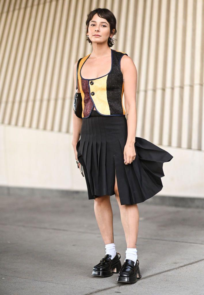 <p>Alyssa Coscarelli plays with prim with an asymmetric pleated skirt and platform loafers. </p>