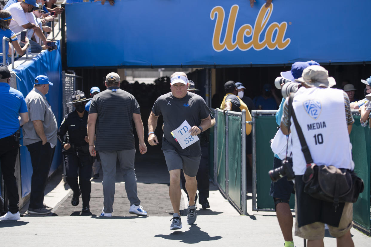 UCLA head coach Chip Kelly jogs to enter the field before an NCAA football game against Hawaii on Saturday, Aug. 28, 2021, in Los Angeles. (AP Photo/Kyusung Gong)