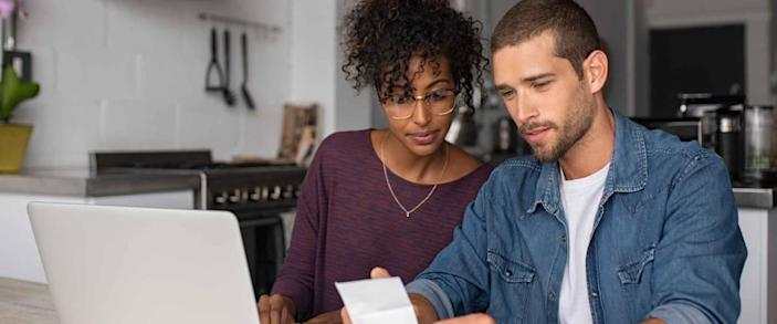 Young couple sitting at table looking at bills