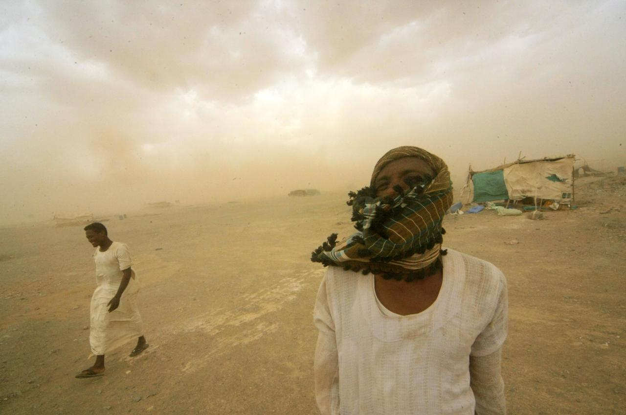 Gold mine workers walk to their shelter during a sandstorm at Al-Ibedia locality in the River Nile State, in this July 30, 2013 file picture. To match Special Report SUDAN-DARFUR/GOLD REUTERS/Mohamed Nureldin Abdallah/Files (SUDAN - Tags: SOCIETY BUSINESS EMPLOYMENT COMMODITIES CIVIL UNREST)