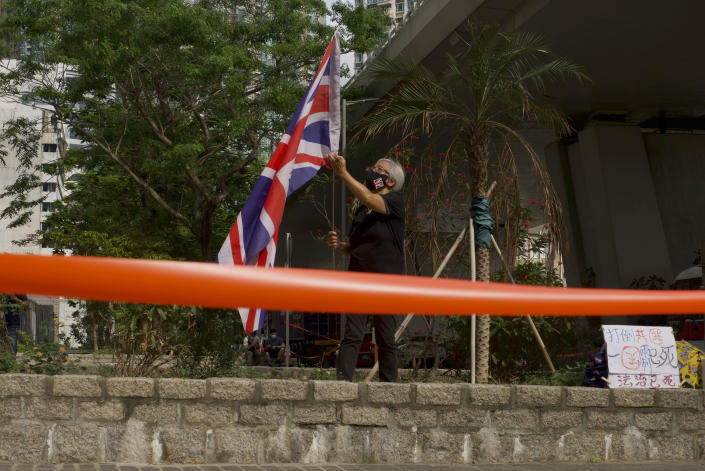 A pro-democracy supporter holds a British flag outside a court in Hong Kong Thursday, April 1, 2021. Seven pro-democracy advocates were convicted Thursday for organizing and participating in an unlawful assembly during massive anti-government protests in 2019, as Hong Kong continues its crackdown on dissent. (AP Photo/Vincent Yu)