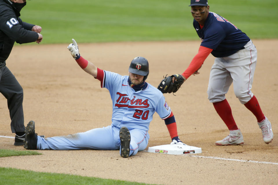 Minnesota Twins' Josh Donaldson calls for time after safely sliding into third base ahead of the tag of Boston Red Sox third baseman Rafael Devers (11) in the first inning in the second baseball game of a doubleheader, Wednesday, April 14, 2021, in Minneapolis. (AP Photo/Andy Clayton-King)