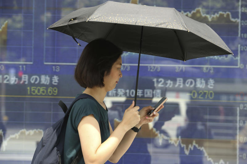 A woman walks by an electronic stock board of a securities firm in Tokyo, Monday, Sept. 2, 2019. Asian stock markets are mixed after Washington and Beijing stepped up their trade war with a new round of tariff hikes. (AP Photo/Koji Sasahara)