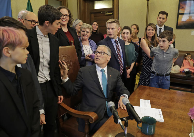 "Washington Gov. Jay Inslee, center, turns to talk with Katrina Spade, upper left, the founder and CEO of Recompose, a company that hopes to use composting as an alternative to burying or cremating human remains, Tuesday, May 21, 2019, at the Capitol in Olympia, Wash., before signing a bill into law that allows licensed facilities to offer ""natural organic reduction,"" which turns a body, mixed with substances such as wood chips and straw, into soil in a span of several weeks. The law makes Washington the first state in the U.S. to approve composting as an alternative to burying or cremating human remains. (AP Photo/Ted S. Warren)"