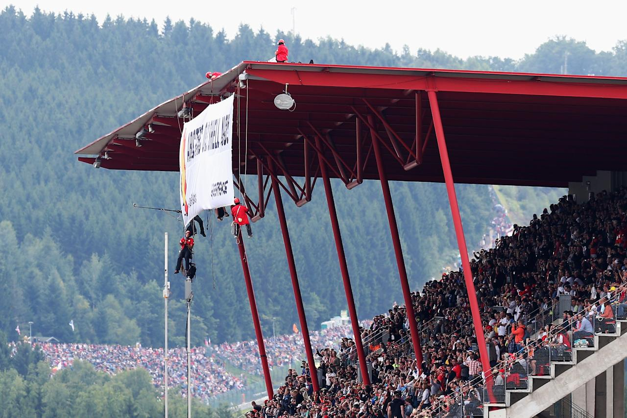 SPA, BELGIUM - AUGUST 25: Demonstrators protest by climbing onto the roof of the main grandstand before the Belgian Grand Prix at Circuit de Spa-Francorchamps on August 25, 2013 in Spa, Belgium. (Photo by Mark Thompson/Getty Images)