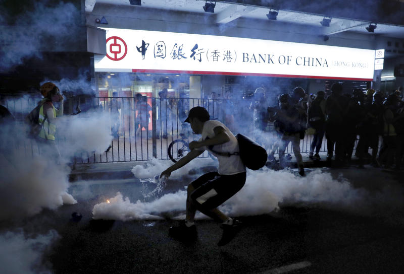 A protester tries to pour water on a tear gas canister as protesters battle with police on the streets of Hong Kong on Saturday, Sept. 21, 2019. Protesters in Hong Kong threw gasoline bombs and police fired tear gas Saturday in renewed clashes over anti-government grievances (AP Photo/Kin Cheung)