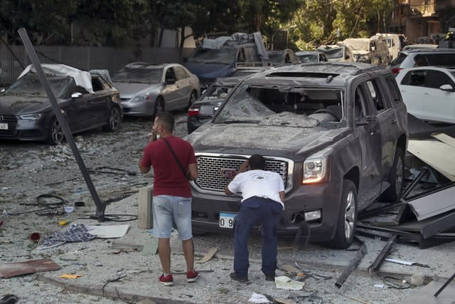 A man inspects his a damaged car after a massive explosion in Beirut