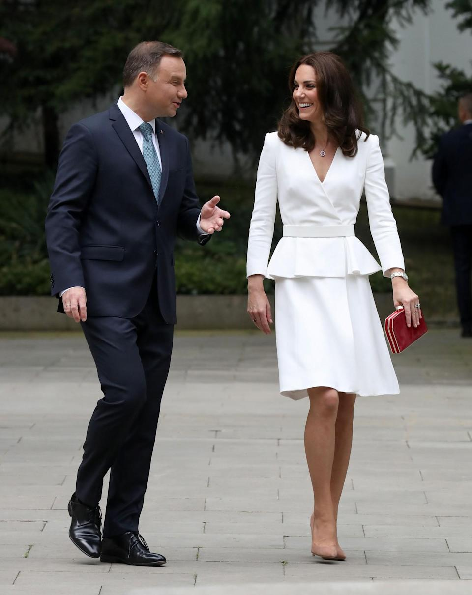 <p>Kate touched down in Poland for the start of the royal tour wearing a white peplum coat by Alexander McQueen. Suede Gianvito Rossi heels dressed her feet and a box clutch in the national colour of Poland – Red – topped off the simple, elegant look.<br><i>[Photo: PA]</i> </p>