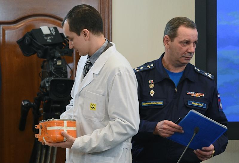A specialist (L) carries the flight recorder from the Russian Sukhoi Su-24 bomber that was shot down by a Turkish jet on November 24 at a briefing in Moscow on December 18, 2015 (AFP Photo/Vasily Maximov)