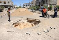 Palestinians check the aftermath of an Israeli air strike in Rafah in the southern Gaza Strip