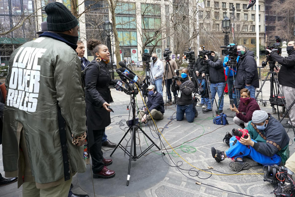 """Keyon Harrold Sr., left, wears a jacket with the words """"Love Over Rules"""" on the back as he listens to Katty Rodriguez, center, speak to reporters during a news conference to announce the filing of a lawsuit against Arlo Hotels and Miya Ponsetto, Wednesday, March 24, 2021, in New York. Keyon Harrold and his son were allegedly racially profiled in an Arlo hotel in Manhattan by Miya Ponsetto in December 2020. Ponsetto wrongly accused Keyon Harrold Jr. of stealing her phone and physically attacking him. (AP Photo/Mary Altaffer)"""