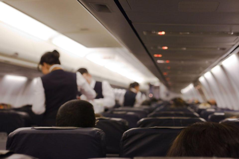 Have you ever wondered why cabin crew welcome you onboard with their hands behind their back? [Photo: Getty]