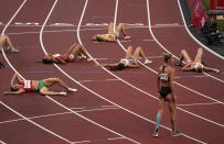 Heptathletes lay on the track after finishing the heptathlon 1500-meters at the 2020 Summer Olympics, Thursday, Aug. 5, 2021, in Tokyo, Japan. (AP Photo/Charlie Riedel)