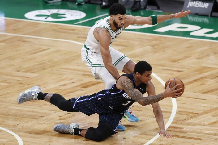Orlando Magic's Chuma Okeke (3) passes off as he falls in front of Boston Celtics' Jayson Tatum during the first half on an NBA basketball game, Sunday, March 21, 2021, in Boston. (AP Photo/Michael Dwyer)