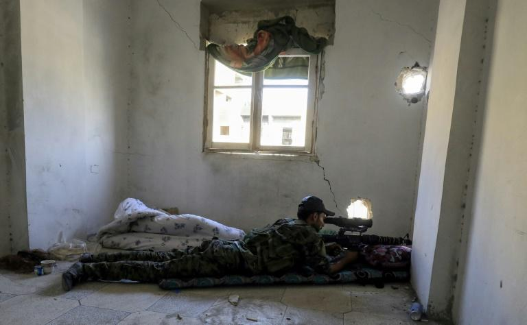 A member of the Syrian Democratic Forces (SDF), a US-backed Kurdish-Arab alliance, looks through the scope of a sniper rifle as he lies in a flat in the al-Daraiya neighbourhood of the embattled northern Syrian city of Raqa on September 5, 2017