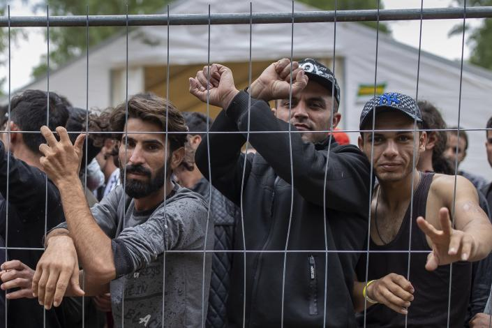 Migrants stand behind a fence inside the newly built refugee camp in the Rudninkai military training ground, some 38km (23,6 miles) south from Vilnius, Lithuania, Wednesday, Aug. 4, 2021. The Red Cross warned Wednesday that Lithuania's decision to turn away immigrants attempting to cross in from neighboring Belarus does not comply with international law. Lithuania, a member of the European Union, has faced a surge of mostly Iraqi migrants in the past few months. Some 4,090 migrants, most of them from Iraq, have crossed this year from Belarus into Lithuania. (AP Photo/Mindaugas Kulbis)