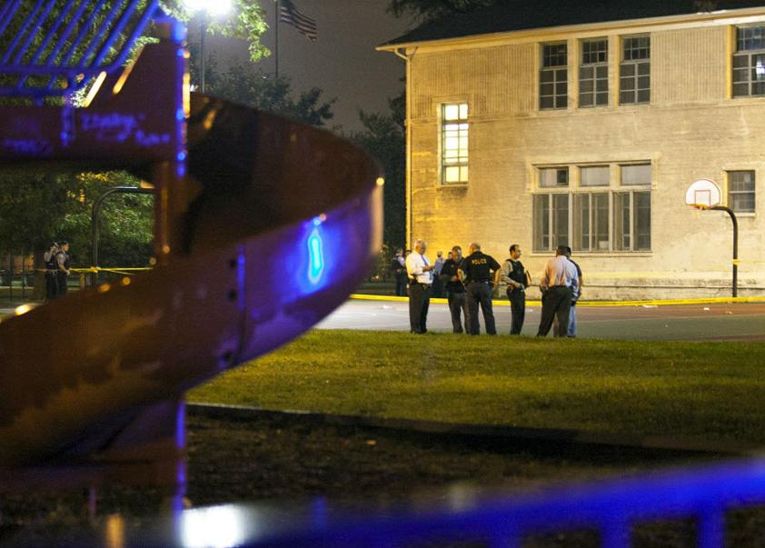 In this Thursday, Sept. 19, 2013, photo, officials convene at the scene of a shooting at Cornell Square Park in Chicago's Back of the Yard neighborhood that left multiple victims including a 3-year-old boy. Thursday night's attack was the latest violence in a city that has struggled to stop such shootings by increasing police patrols. (AP Photo/Sun-Times Media, Chandler West)
