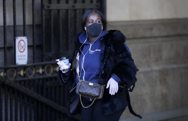 A woman wears a mask and gloves as she leaves a station in London. (AP)