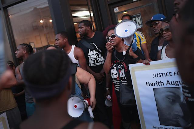 <p>Demonstrators rally outside the Sideline Studio Barber & Beauty Salon in the South Shore neighborhood protesting the shooting death of 37-year-old Harith Augustus who worked there as a barber on July 16, 2018 in Chicago, Ill. Augustus was shot and killed on July 14 by a Chicago police officer following a brief altercation. Two people were shot a block from where Augustus was killed less than an hour before tonight's protest began. (Photo: Scott Olson/Getty Images) </p>