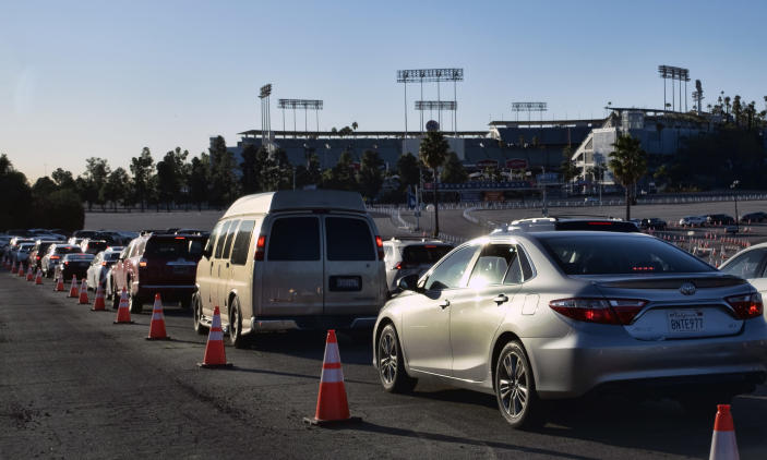 Los Angeles residents wait in line in their cars during the early morning to receive a COVID-19 vaccine at Dodger Stadium, in Los Angeles on Tuesday, Jan. 26, 2021. California is revamping its vaccine delivery system to give the state more control over who gets the shots following intense criticism of a slow and scattered rollout by counties. (AP Photo/Richard Vogel)