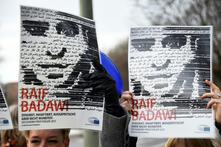 Amnesty International hold up portraits of jailed Saudi blogger Raif Badawi in front of the Saudi embassy Berlin in January 2016