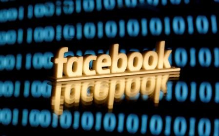 FILE PHOTO: Facebook logo is seen in front of displayed binary code in this illustration picture