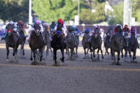 Jockey John Velazquez, center in red cap, aboard Medina Spirit, leads the field to win the 147th running of the Kentucky Derby at Churchill Downs, Saturday, May 1, 2021, in Louisville, Ky. (AP Photo/Michael Conroy)