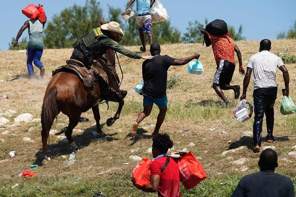 A United States Border Patrol agent on horseback tries to stop a Haitian migrant from entering an encampment on the banks of the Rio Grande near the Acuna Del Rio International Bridge in Del Rio, Texas, on 19 September 2021