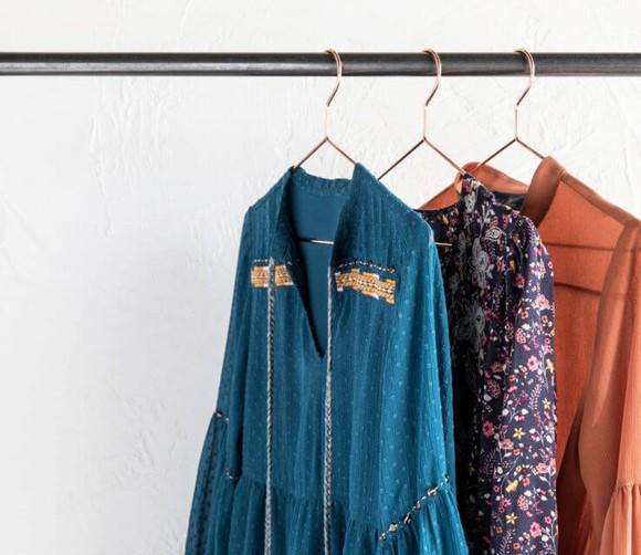 Three blouses hanging on a rack.