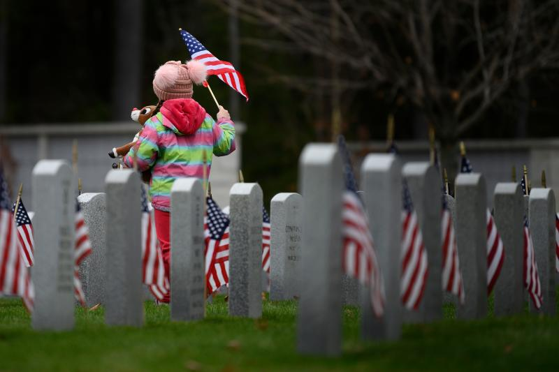 Molly Jakubowski waves a flag as she walks through the New Hampshire State Veterans Cemetery in Boscawen, New Hampshire, on Nov. 11, 2019, during a Veterans Day service. (Photo: Jim Watson/AFP via Getty Images)