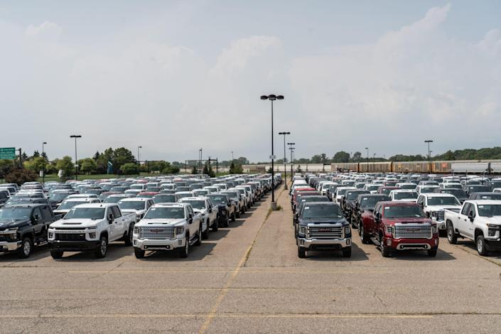 General Motors trucks sit in a gated parking lot next to the Economy Lot across from Bishop International Airport in Flint on August 11, 2021.
