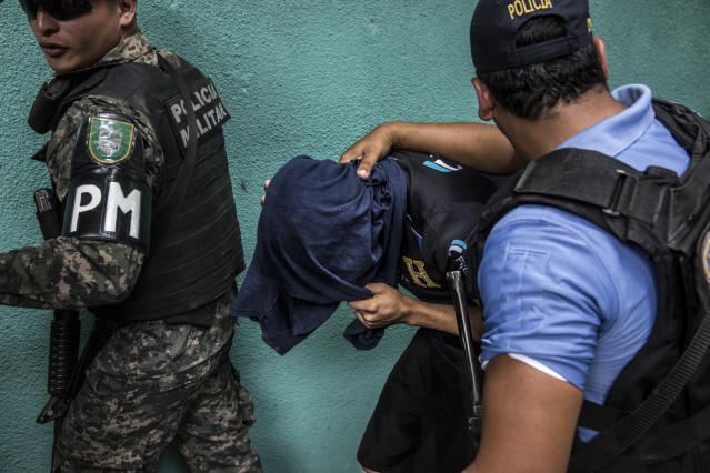 <p>During a military police operation in Hato de Enmedio neighborhood in the capital Tegucigalpa, a young men allegedly belonging to the 18th street criminal gang, or Mara-18, is escorted away. (Photo: Francesca Volpi) </p>